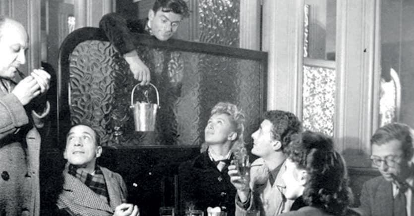 Al café de flore. Jean Paul Sartre, seduto a destra con la pipa in bocca.