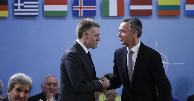 Il segretario generale della Nato Jens Stoltenberg  (a destra) dà il benvenuto al rappresentante del Montenegro Igor Luksic (Epa)