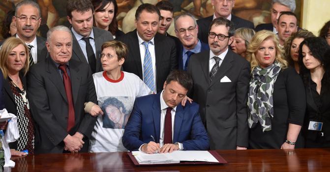 Il presidente del Consiglio Matteo Renzi firma la legge sull'omicidio stradale attorniato da alcuni familiari di vittime della strada (Ansa)