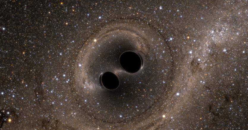 Un'illustrazione ci mostra i due buchi neri che ruotano uno attorno all'altro prima della loro fusione