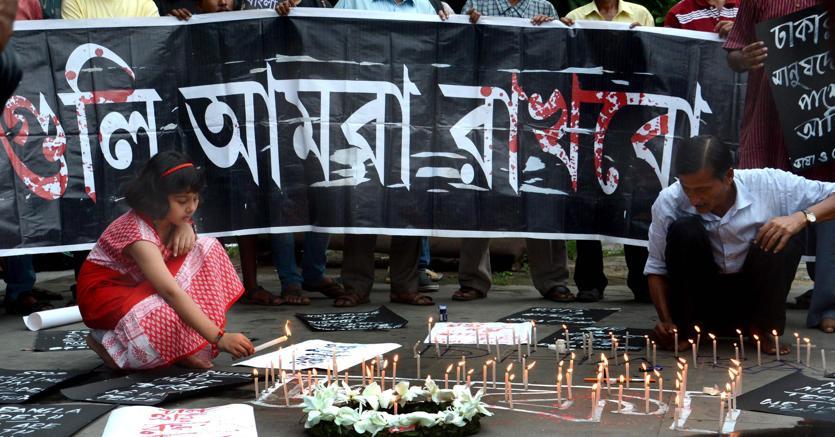 Attivisti indiani accendono candele durante le preghiere per le vittime dell'attacco terroristico a Dacca