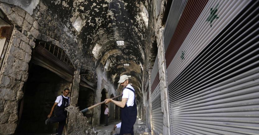 Membri del Programma Onu per lo sviluppo al lavoro nel mercato di Homs, gravemente danneggiato (Afp)