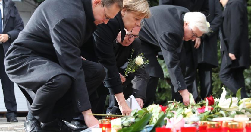 Angela Merkel depone un mazzo di fiori sul luogo dell'attentato (Epa)