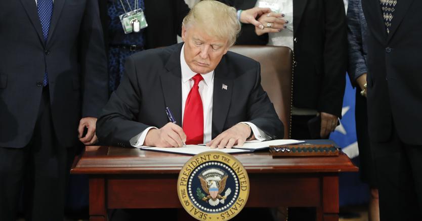 Donald Trump mentre firma un ordine esecutivo sull'immigrazione