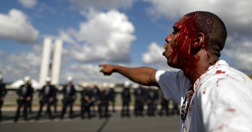 Manifestante ferito a Brasilia. Sullo sfondo le forze di polizia schierate (Reuters)