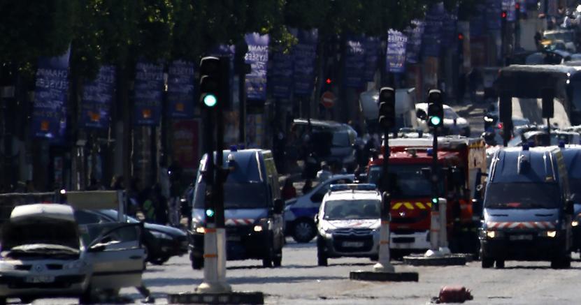 L'auto sospetta, a sinistra, durante l'operazione di polizia sugli Champs-Elysee (AP Photo/Matthieu Alexandre)