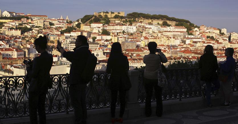 Turisti davanti al panorama della vecchia Lisbona (Ap)