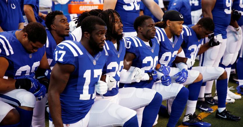 I giocatori degli Indianapolis Colts in ginocchio durante l'esecuzione dell'inno americano