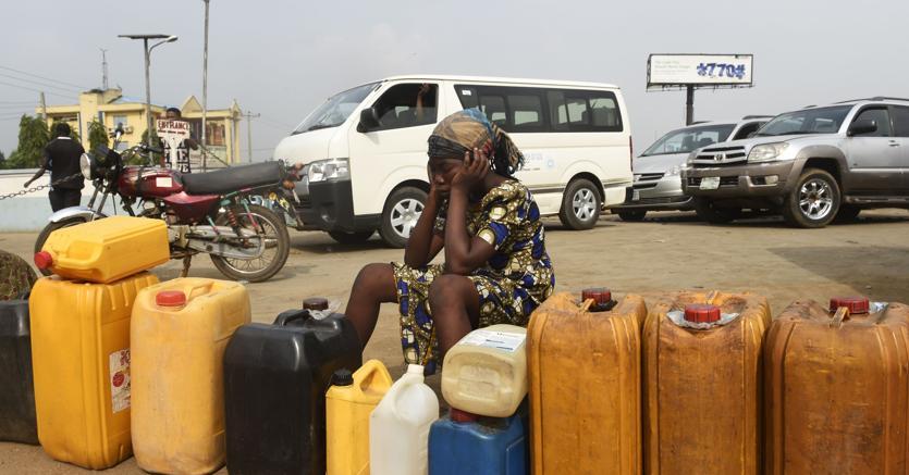 Una donna in coda per acquistare benzina a Lagos, Nigeria