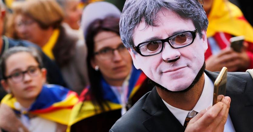 Un manifestante a Barcellona con la maschera del  leader catalano Puigdemont (Afp)