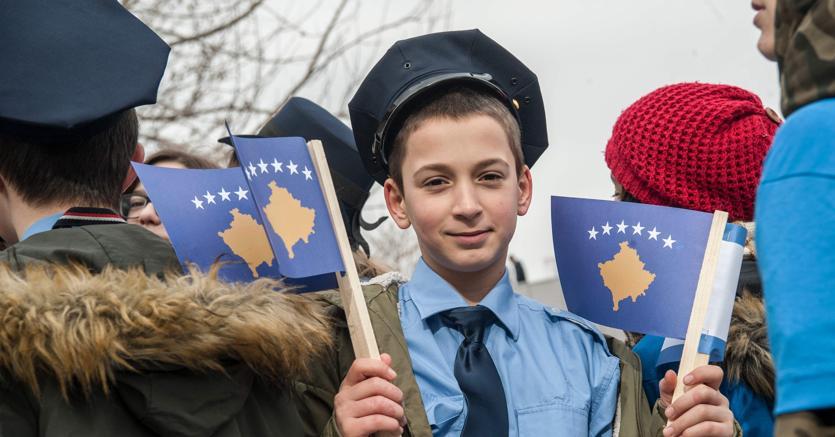In cammino. Un ragazzino vestito da poliziotto a Pristina