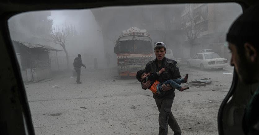 Un volontario soccorre un bambino nel Ghouta orientale, in Siria, sottoposto a massicci bombardamenti