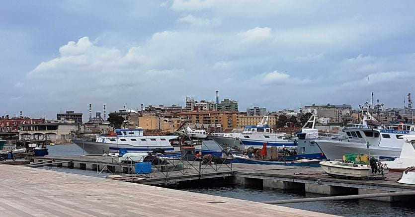 Taranto, il colpo d'occhio dal mare piccolo: pescherecci, il quartiere Tamburi e, sullo sfondo, le ciminiere dell'Ilva