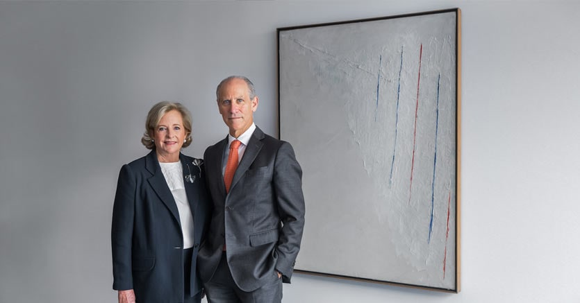 Patricia Phelps de Cisneros e Glenn D. Lowry, direttore del MoMA, di fianco all'opera di Alejandro Otero, Colored Lines on White Background, 1950, olio su tela, 130,2 × 97,2 cm, Courtesy The Museum of Modern Art, New York