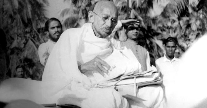Il Mahatma Gandhi mentre legge un giornale