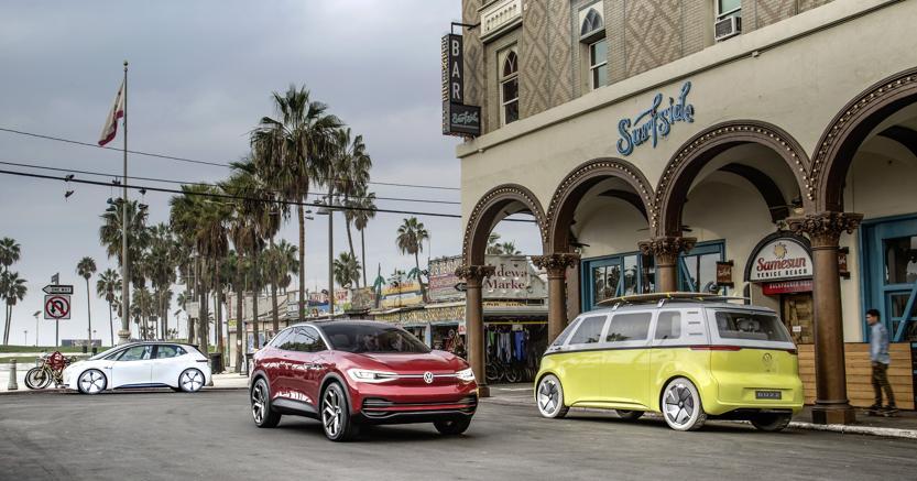 Nell'immagine uno scenario full electric con tre modelli della gamma alla spina I.D. di Volkswagen che, ancora in fase prototipale,  rappresentanola terza era della marca tedesca dopo il Maggiolino e la Golf . E c'è (a destra ) il furgone dei figli dei fiori in versione elettrica