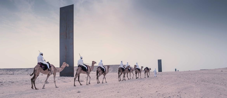 Carovana di cammelli passa accanto all'opera «East-West, West-East» di Richard Serra