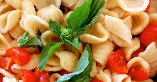 Orecchiette fatte in casa condite con pomodorini e basilico