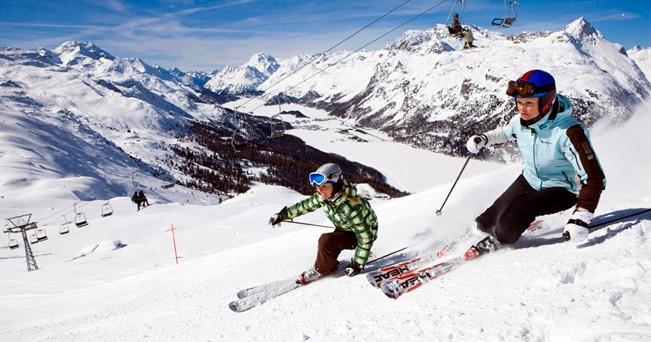 Due sciatrici sulla pista Giand' Alva, nella regione del Corvatsch. Sullo sfondo, i laghi di Silvaplana e di Sils (foto Engadin St. Moritz/swiss-image.ch/Daniel Martinek)