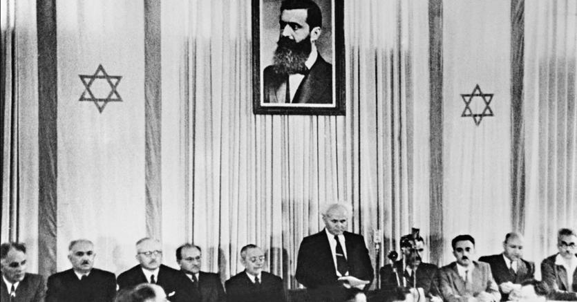 Il primo ministro David Ben Gurion, il 14 maggio 1948, dichiara l'indipendenza dello Stato d'Israele, a Tel Aviv. Alle sue spalle, il ritratto di Theodor Herzl, fondatore del sionismo politico