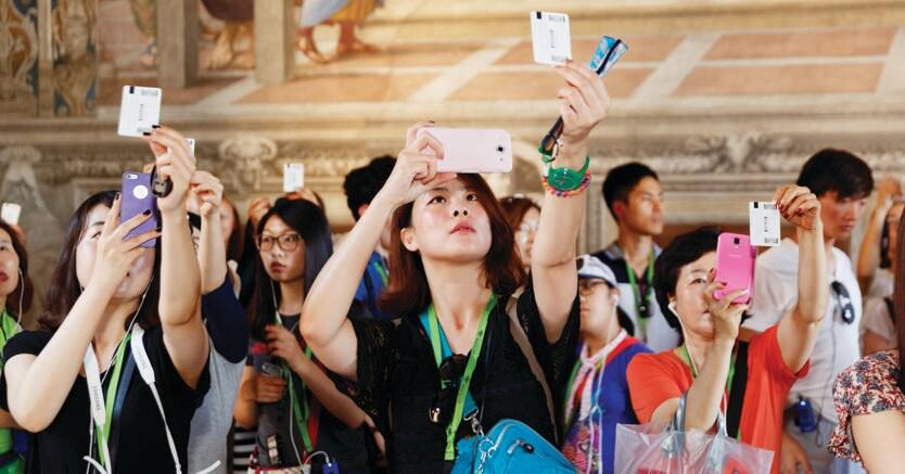 Il fotografo osserva le masse dei visitatori dei Musei Vaticani: nelle Stanze di Raffaello essi fotografano gli affreschi mettendoli a confronto con l'immagine riprodotta sul loro biglietto