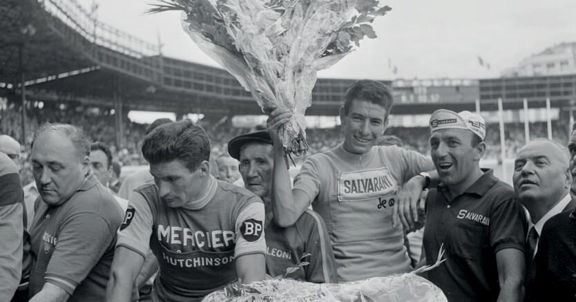 Felice Gimondi, trionfatore del Tour de France 1965 a soli 22 anni, solleva il mazzo di fiori destinato al vincitore.A sinistra, un corrucciato Raymond Poulidor, eterno secondo