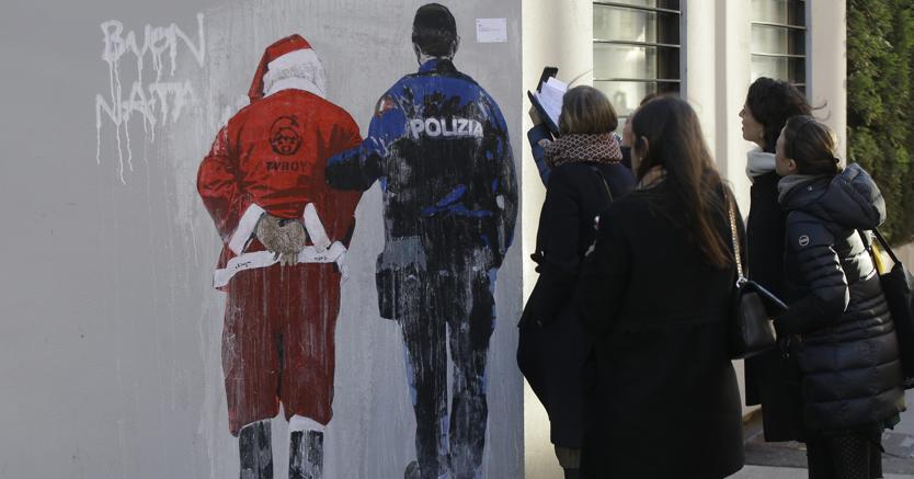 """La gente guarda un murale dipinto dal pittore di pop art Tv Tvboy che mostra un agente di polizia che scorta un Babbo Natale ammanettato, a Milano. Il piccolo cartello in alto a destra recita: """"Permesso di soggiorno negato per Babbo Natale""""  (Ap)"""