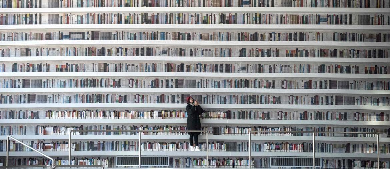Perdersi nella lettura . Una ragazza scatta foto nella Tianjin Binhai Library, l'avveniristica biblioteca caratterizzata dalle linee sinuose degli scaffali e da lunghe distese di libri