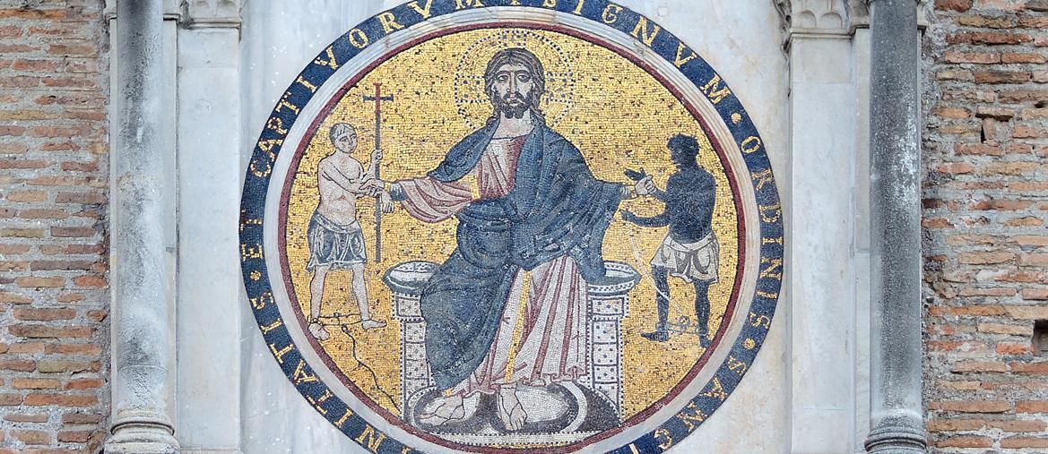 Un singolare mosaico del XIII secolo mostra Cristo che libera  e attira  a sé sia  il prigioniero cristiano bianco che quello pagano con la pella scura. Roma,  facciata della chiesa  di San Tommaso  in Formis