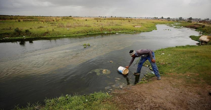 Un uomo raccoglie dell'acqua dal un fiume a Cape Town, in Sud Africa (foto Reuters)