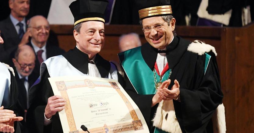 Mario Draghi con la laurea honoris causa, al suo fianco il rettore dell'Università di Bologna Francesco Ubertini (Ansa)