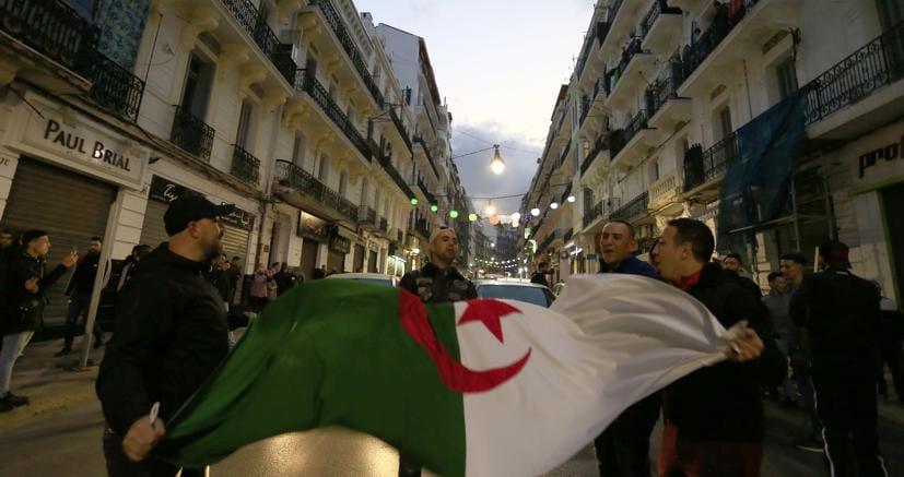 Cittadini algerini festeggiano in strada dopo il passo indietro di Bouteflika, che ha rinunciato a ricandidarsi (Reuters)