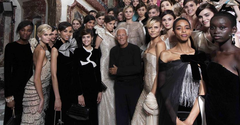 Giorgio Armani con le modelle di una sua sfilata  (credit SGP)