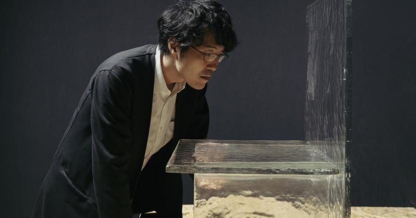 Oki Sato, fondatore e chief designer di Nendo con un pezzo della collezione Melt per WonderGlass
