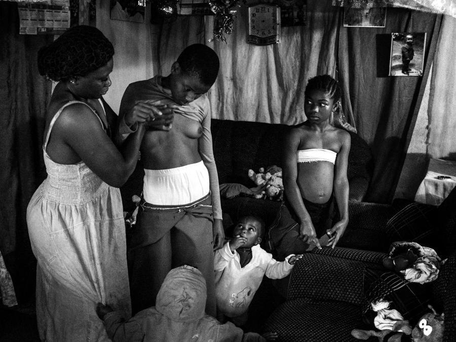 """Heba Khamis, premio  'Contemporary Issues - Stories'. Veronica, 28 anni, massaggia il seno della figlia di 10  anni Michelle a Bafoussam, Camerun, 7 novembre 2016. La madre  cerca di stirare il seno della figlia per non farla diventare """"adulta"""" e potenziale madre, come l'altra figlia madre a 14 anni  EPA/HEBA KHAMIS"""