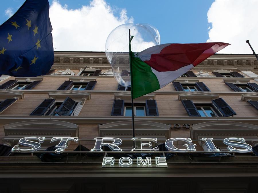 The St. Regis Rome festeggia il suo 125° compleanno con un rinnovo costato 40 milioni di euro. Gli interni sono stati disegnati dall'architetto francese Pierre Yves Rochon. L'hotel ha posizione strategica vicino a Piazza della Repubblica e al Quirinale. Le bolle sopra le bandiere sono un'opera d'arte di Loris Cecchini