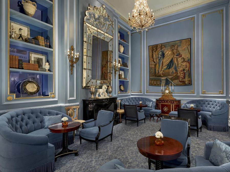La biblioteca blu zaffiro è una saletta separata ma collegata alla lobby, con lampadari in cristallo, specchio veneziano e camino in marmo nero