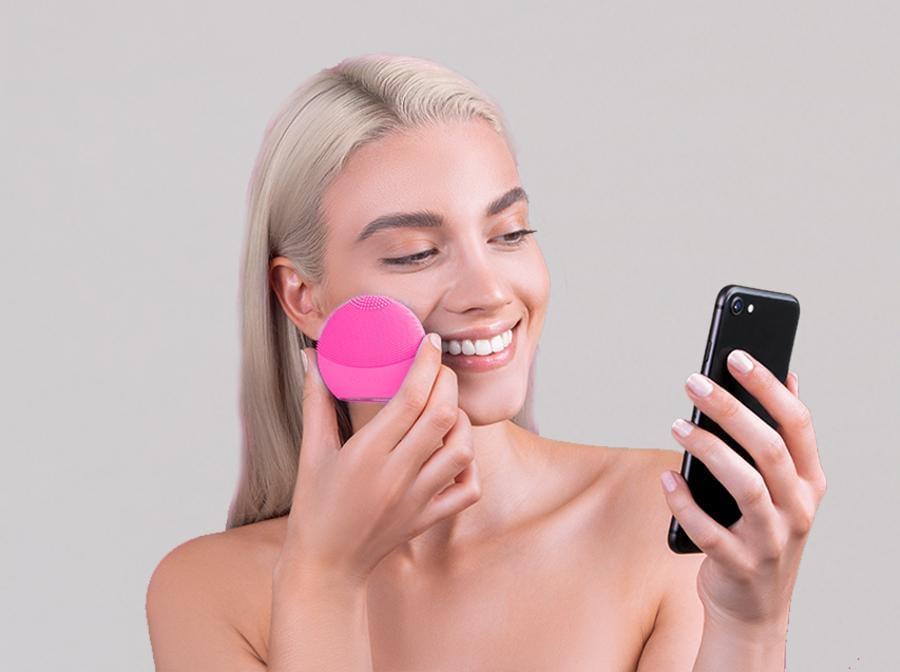 """Foreo, il brand svedese amatissimo dalle millennial (e non soltanto da loro), pioniere del Beauty Tech, inaugura l'era della cosmesi personalizzata lanciando LUNA fofo, l'ultimo nato nella famiglia LUNA con A.I. integrata: LUNA fofo, che può serenamente essere definito """"il più piccolo e smart personal beauty coach al mondo"""", è il nuovo beauty gadget FOREO che rivoluziona l'industria del settore incorporando funzionalità̀ di apprendimento automatico e personalizzazione. Usarlo è semplicissimo, soprattutto grazie alla app tramite la quale si crea il profilo utente (Skin Profile). Foreo LUNA fofo tiene monitorate le condizioni della pelle, aiuta ad applicare i cosmetici e suggerisce eventuali modifiche nella beauty routine."""
