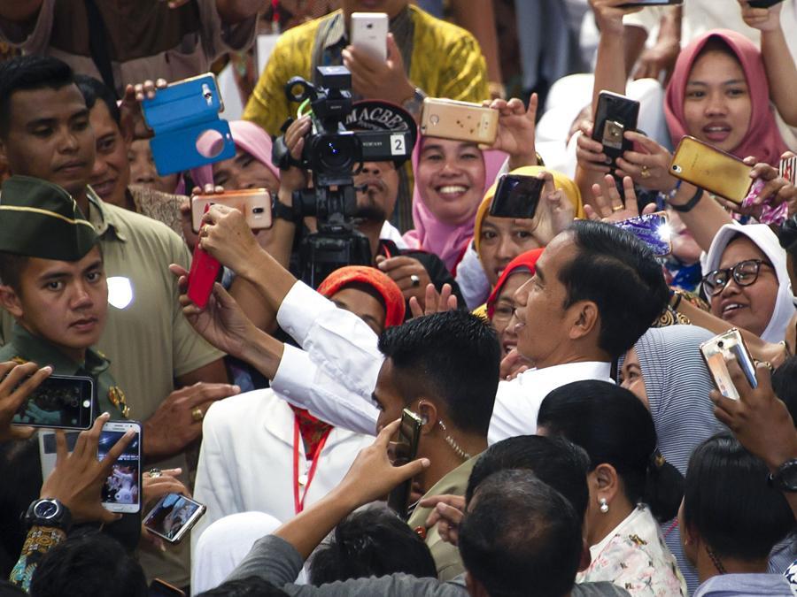 Il president Joko Widodo si fa un selfie tra i suoi supprter. (Photo by JUNI KRISWANTO / AFP)