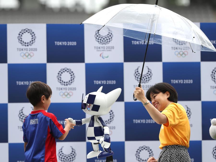 Un ragazzo stringe la mano al robot-mascotte  Miraitowa (Photo by Behrouz MEHRI / AFP)