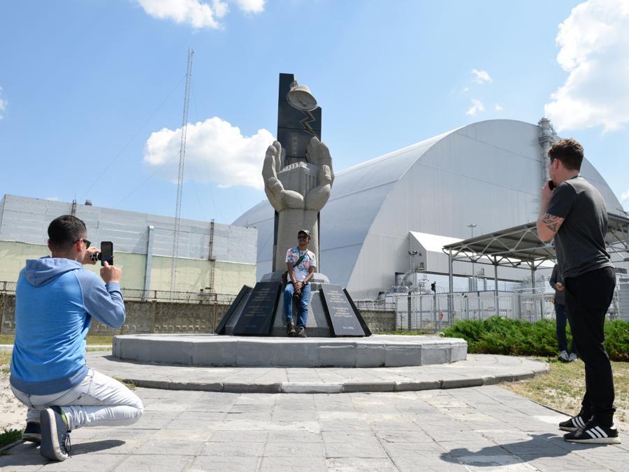 Turisti fotografano il monumento eretto in memoria delle vittime del disastro nucleare a Chernobyl  (Stringer / Sputnik)