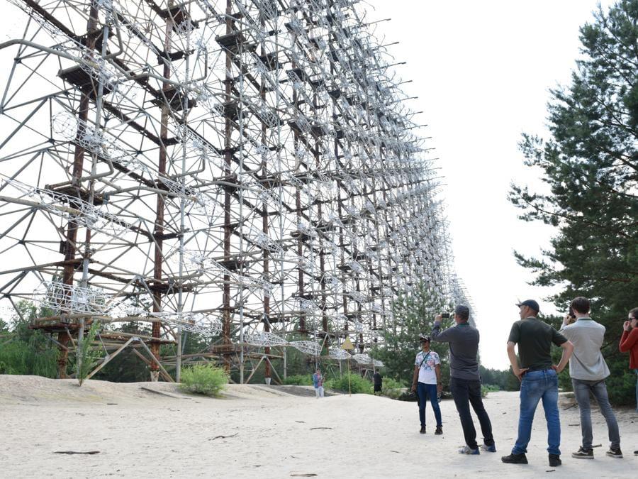 Turisti osservano Duga3 nelle vicinanze di Chernobyl, si tratta di un sistema radar sovietico costruito con lo scopo di intercettare eventuali attacchi missilistici  (Stringer / Sputnik)