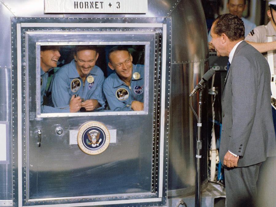 24 luglio 1969,  il presidente Richard Nixon con, in quarantena,  Neil Armstrong, Michael Collins e Edwin Aldrin Jr. (Afp)