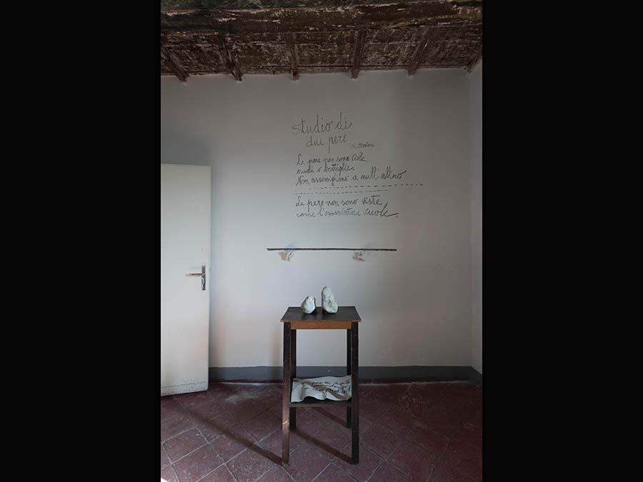 Paolo Icaro, «Two pears, guardare e vedere» 2019. Scritta su muro con carbone, gesso, pietre, comodino in legno, cartone