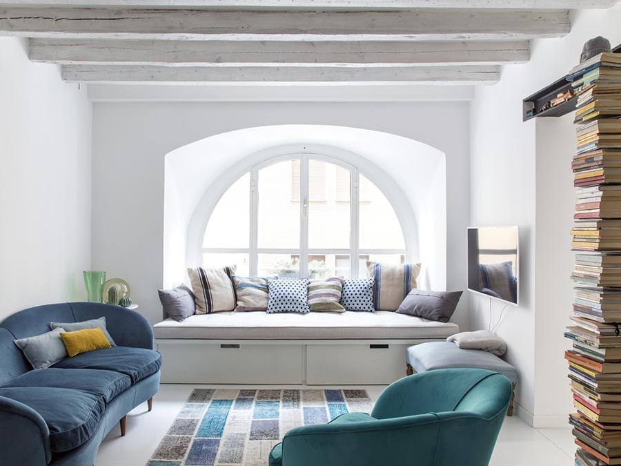 Casa privata, progetto Clara Bona, Studio 98. Sotto la grande finestra ad arco, una pedana con cassettoni fa da divano e, quando serve, da letto ospiti. Qui è stato scelto di fare tutto bianco, pareti, soffitti e pavimento in resina, per far sembrare grandi gli spazi davvero minimi (Giulio Oriani)