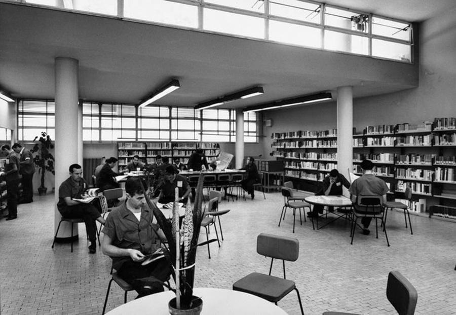Operai e impiegati consultano libri e giornali nella biblioteca dello stabilimento