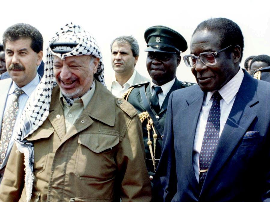 Il presidente dello Zimbabwe Robert Mugabe (destra) e il suo omologo palestinese Yasser Arafat arrivano nella capitale per partecipare al Vertice mondiale World Solar Summit, Zimbabwe, 15 settembre 1996. REUTERS/File Picture