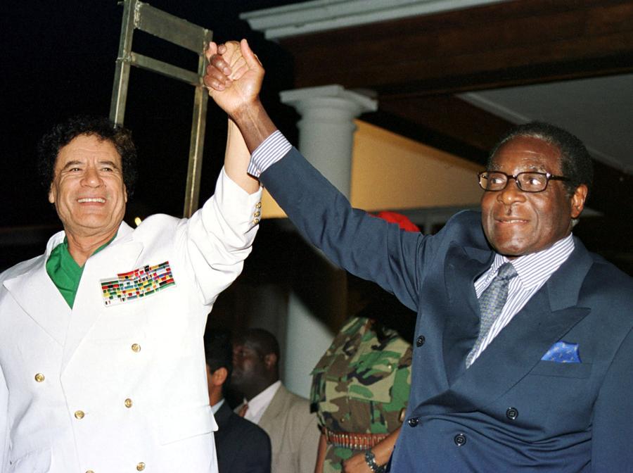 Il leader libico, il colonnello Muammar Gheddafi (sinistra) e il presidente dello Zimbabwe, Robert Mugabe, salutano i sostenitori fuori dalla State House di Harare, Zimbabwe, 12 luglio 2001. REUTERS/Stringer/File Photo