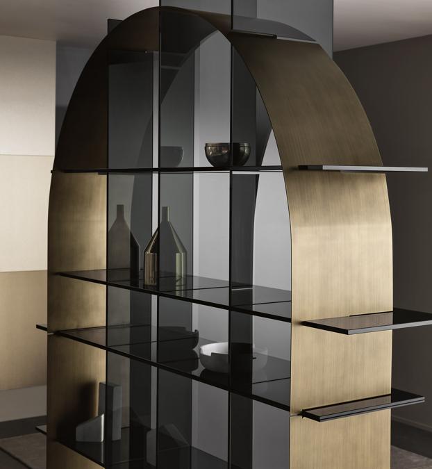 Paradigma di De Bona / De Meo per Tonelli Design. Libreria freestanding composta da una griglia centrale realizzata in vetro e da una componente geometrica ad incastro in lamiera sottile disponibile nella forma di arco o cerchio, con finitura a contrasto in bronzo spazzolato o nella nuova versione nero spazzolato. Il vetro può essere extrachiaro o fumè