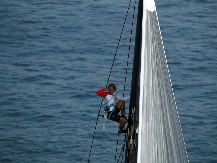 Un concorrente si arrampica su un albero mentre le barche a vela competono durante la regata Barcolana di fronte al porto di Trieste (REUTERS/Alessandro Garofalo)